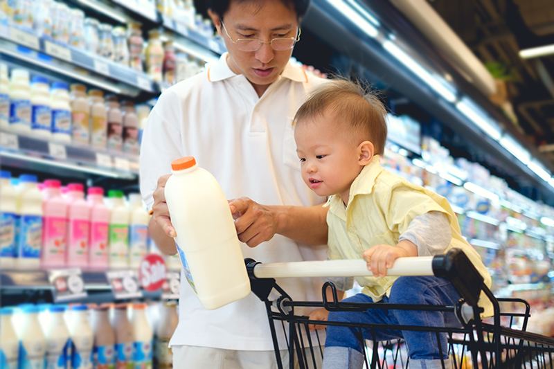 Asian Father & Cute little 18 months old toddler boy child choosing milk product in grocery store.