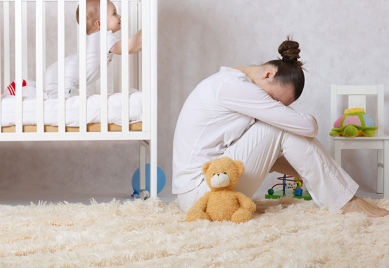 Mother depressed by baby in crib.