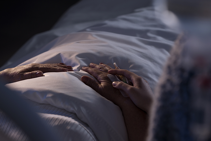 older person in bed - view of hands and bedding.