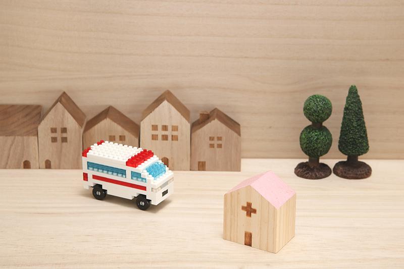 Lego ambulance near houses