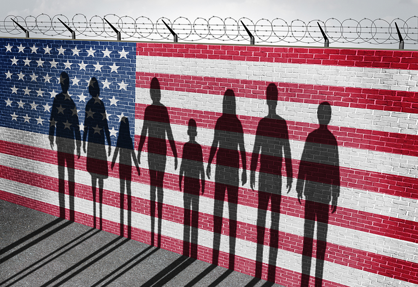shadow of people against a wall with American flag and barbed wire.