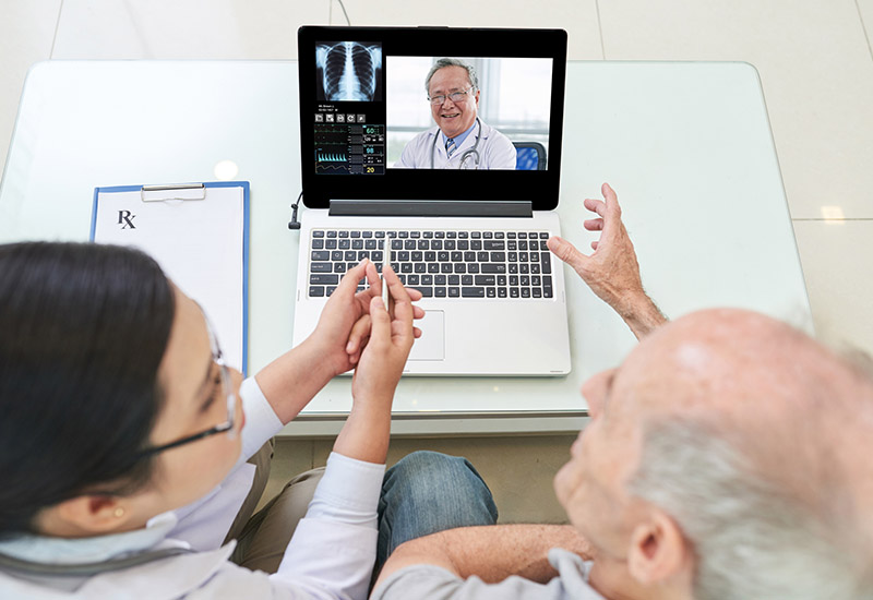 man and woman looking at doctor on a computer