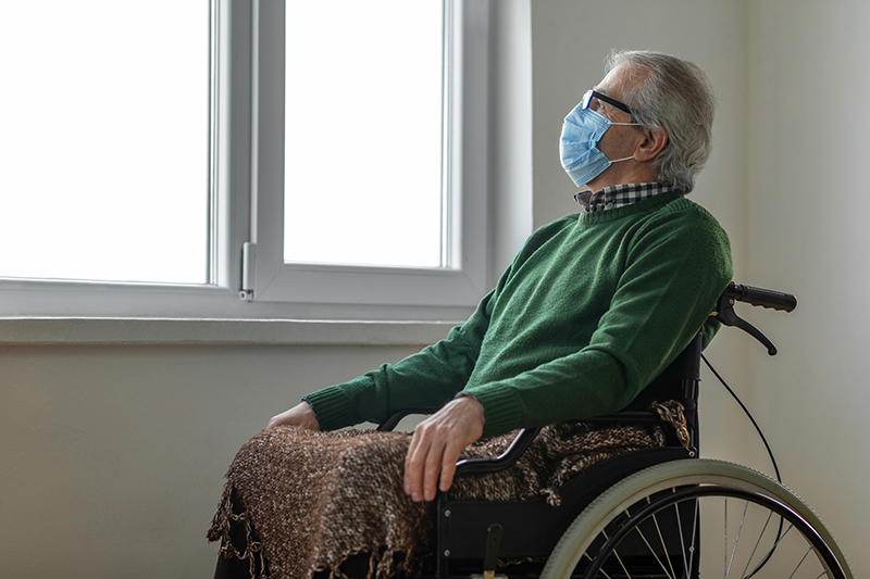 senior man in wheelchair with mask looking out window
