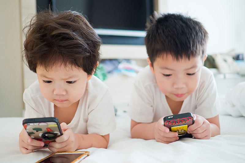 two young children on cell phones