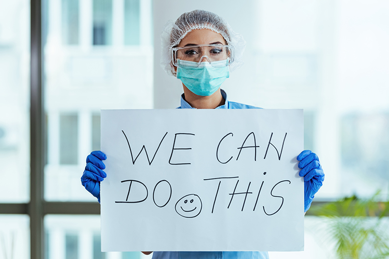 """Woman holding """"we can do it"""" sign"""
